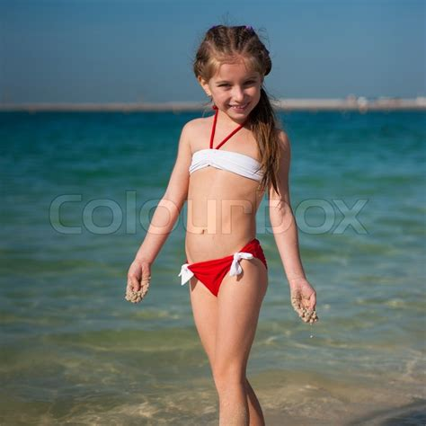preteen camel toe cute little girl in red and white swimsuit on the beach