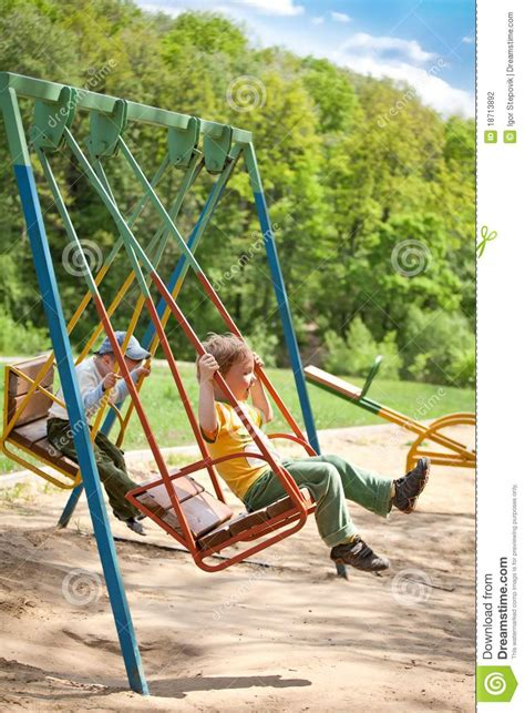 swing at the park two boy swinging on a swing in the park stock photography