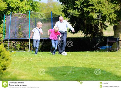 backyard boys grandfather and grandsons playing soccer in the garden