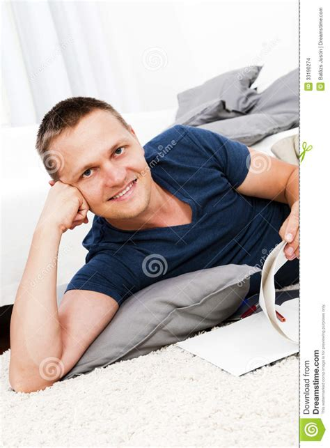 read comfortably a handsome man sitting on the floor in the living room
