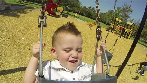 age for baby swing at park happy baby boy in swing at park on sunny summer day hd