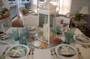 beach themed table setting with sailboat napkin fold and shell centerpiece