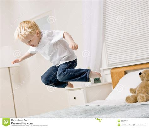 jumping bed boy jumping in mid air on bed in bedroom stock photo