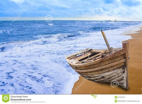 fishing boat on the beach old fishing boat stranded on a beach in sunny day stock