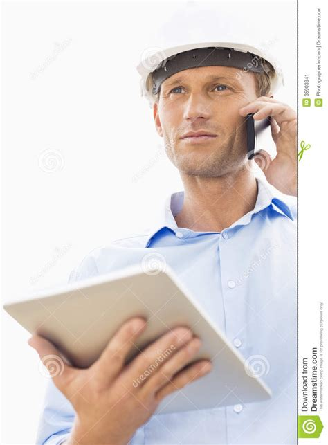 male architect with digital tablet studying plans in low angle view of male architect with digital tablet using
