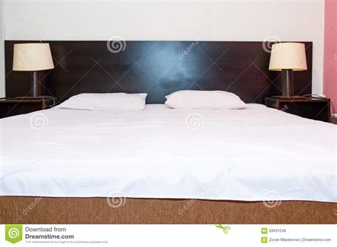 two pillows on bed stock photo image of domestic room bed with white sheets and pillows with two bedside l on