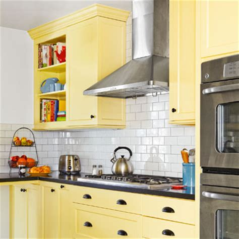 backsplash for yellow kitchen a kitchen redo with added function and lots more charm yellow cabinets white subway tile