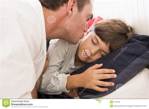 boy kissing a girl in bedroom man waking young boy in bed with kiss stock photo image