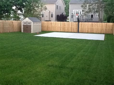 beautiful green grass surrounds a new basketball court a