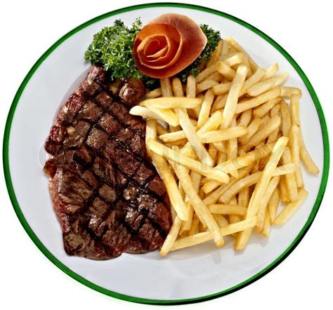 Hotplate Steak Potatoes steak with fried potatoes on a white plate stock photo colourbox