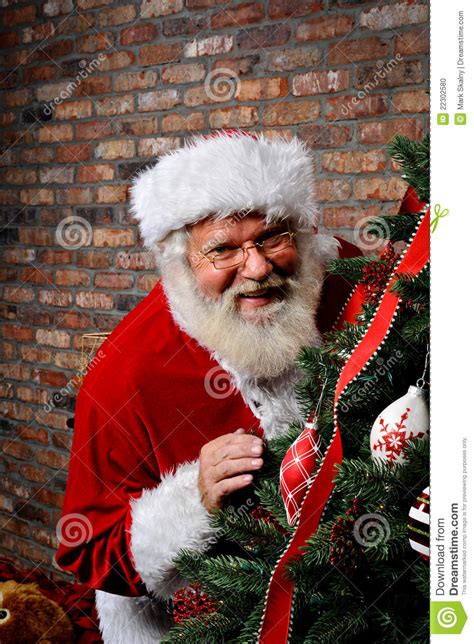 santa claus smiling by the christmas tree stock photo