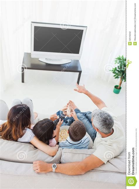 family watching tv with popcorn in living room stock photo family with popcorn watching their television on sofa