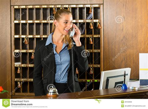 reception of hotel desk clerk taking a call stock image