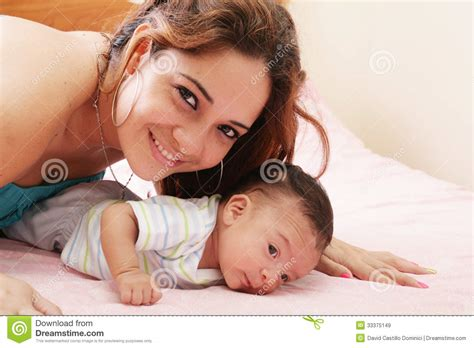 bed moms mom lying down on bed and holding her infant son royalty free stock images image