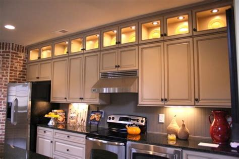 artistic lighting above kitchen cabinets using soft yellow