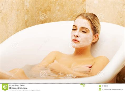 bathroom facial woman relaxing in bath with face mask stock photo image