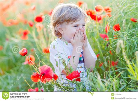 Warm Summer kid boy with poppy flower on poppy field on warm