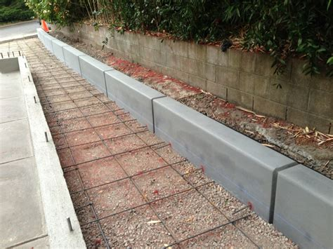 concrete retaining wall with a regular broom finish and four foot joints spaced out yelp