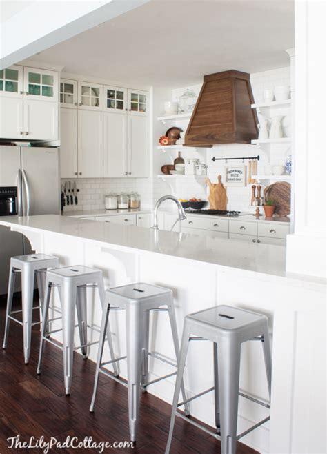 white symmetrical kitchen range with natural wooden wood range hood the lilypad cottage