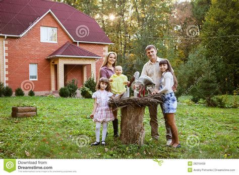 family sitting in backyard of new home royalty free stock