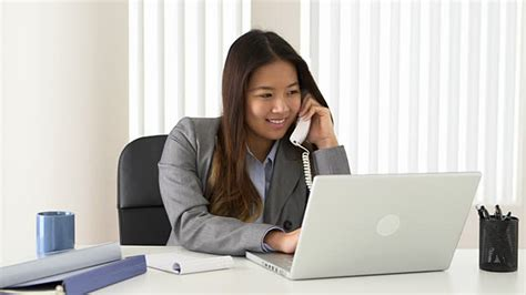 At Desk by Businesswoman Talking On Phone While Working At Desk
