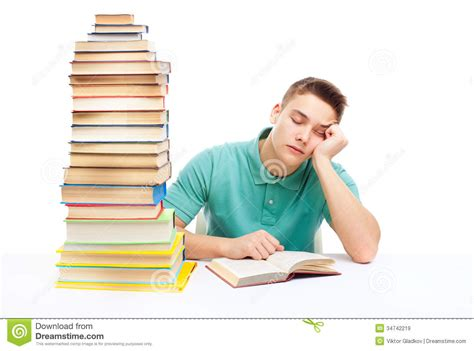 Young Tired Student Sitting At The Desk With High Books Student Sitting At Desk