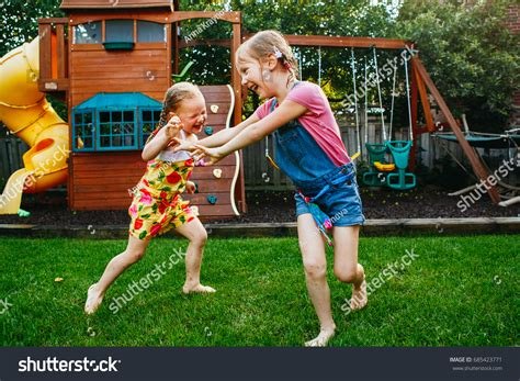 backyard babes portrait two little girls sisters fighting stock photo