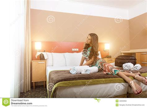 the bed sitting room young woman sitting in the bed of a hotel room stock photo