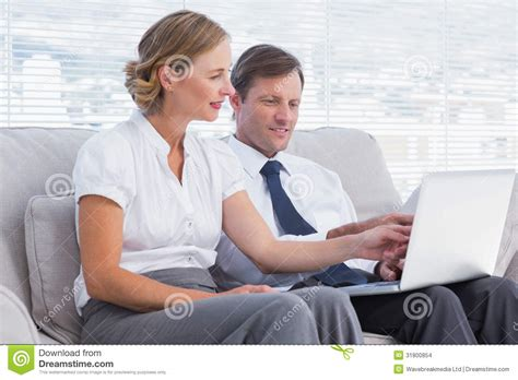 people sitting on a couch business people watching something on laptop stock images