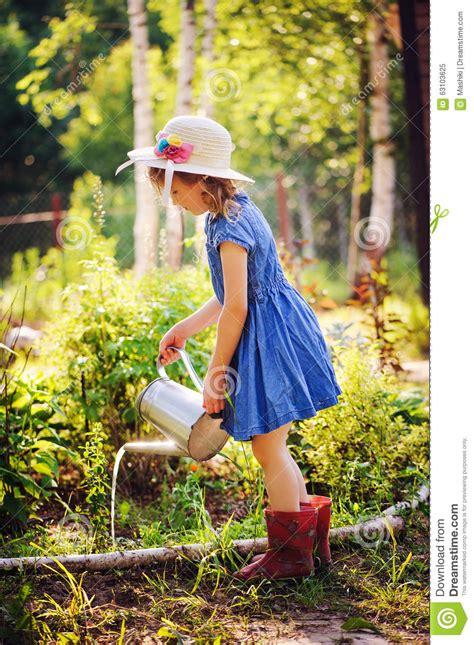 girl watering flowers child girl watering flowers in summer garden little