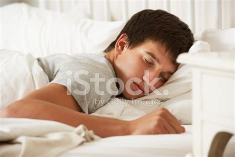 boy sleeping on bed stock foto getty images teenage boy asleep in bed at home stock photos