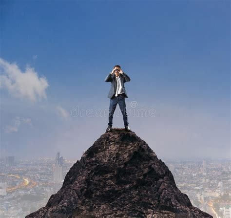 man standing on mountain top young business man standing on top of mountain and spying
