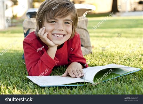 what to get a 7 year old boy for christmas 7 year boy lying on the grass reading a book stock photo 84508765