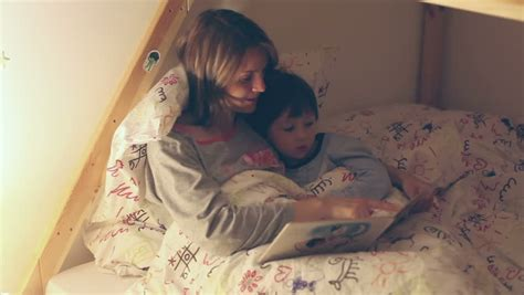 reading before bed mother and child reading a book before bed time stock