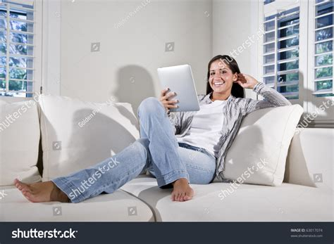 relaxing on the couch hispanic woman reading electronic book relaxing stock