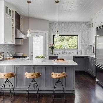 gray distressed kitchen cabinets with marble herringbone gold and gray kitchen with jonathan adler rio pendants