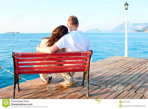 sitting the bench love couple sitting on bench by the sea embracing stock image image 32771241