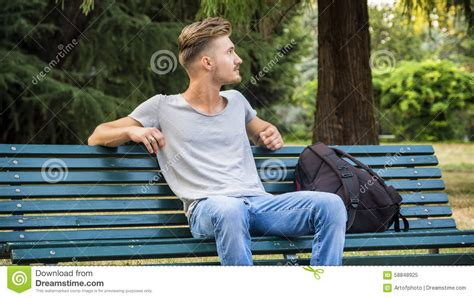 guy sitting on bench handsome blond young man sitting on park bench stock image