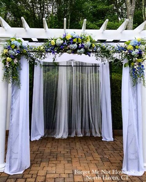 pergola decorated with fabric and floral arrangements for