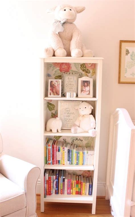 white bookshelf lined with anthropologie floral wallpaper