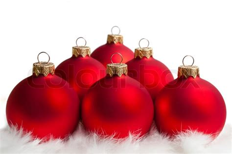 six red christmas tree balls on white fur stock photo