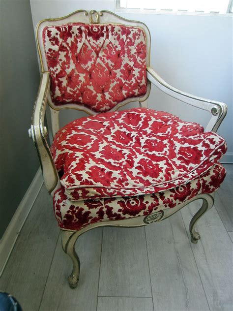 antique white dresser with gold trim french hibriten arm chair red floral textile white gold