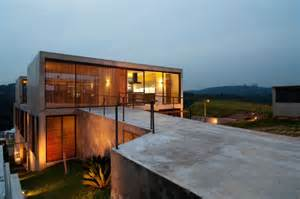 Contemporary Outdoor Fireplaces - hillside house with 2 concrete volumes 2nd story entrance bridge