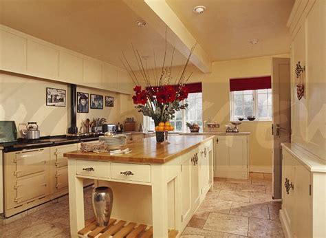 Image: Island unit with wood worktop in modern cream kitchen with cream double Aga   EWA Stock