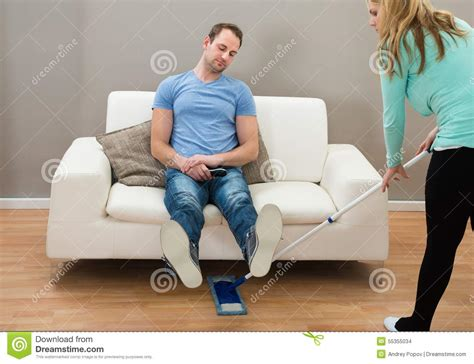 the men on my couch woman cleaning floor while man on sofa stock photo image