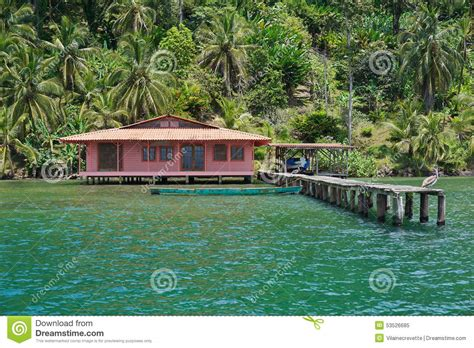 house over water tropical home over water with dock and lush shore stock