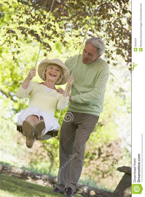 young couple swinging couple outdoors with tree swing smiling stock images