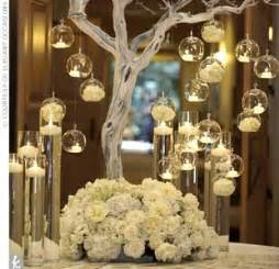 Tree centerpiece with tea lights surrounded by flowers wedding