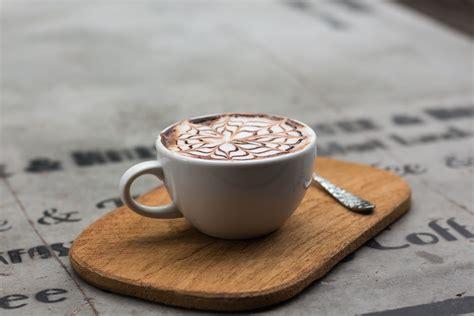 Minuman Luwak White Coffee 20gr white ceramic mug filled with black liquid beside baked bread on ceramic saucer 183 free stock photo