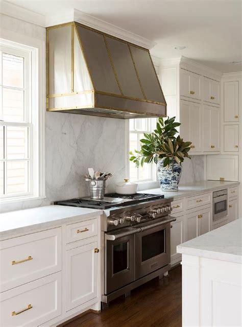 small white kitchen with steel hood kitchen hood between windows design ideas